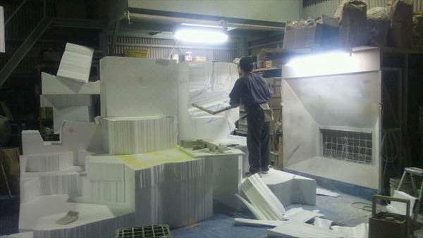 大きな発泡スチロールの塊を削る造形職人